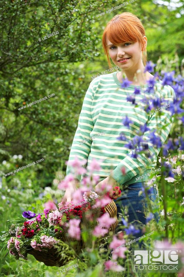 Stock Photo: Woman holding basket of flowers in garden portrait.