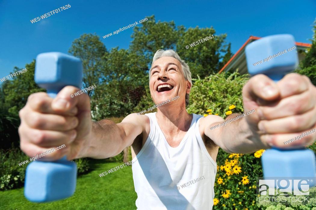 Stock Photo: Germany, Bavaria, Mature man doing exercise with dumbbells.