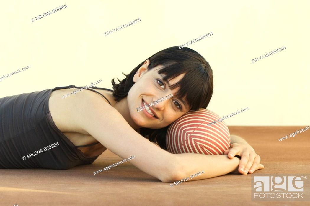 Stock Photo: Woman lying on the ground, resting head on ball, smiling at camera.