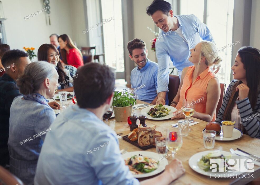 Stock Photo: Waiter serving food to friends dining at restaurant table.
