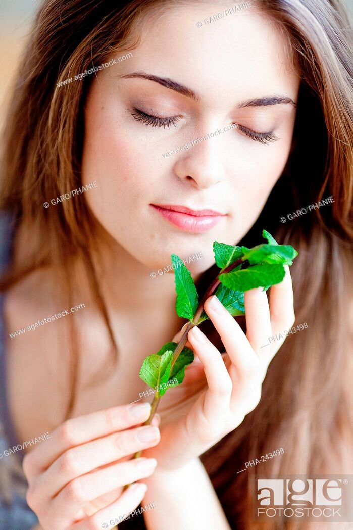 Imagen: Woman smelling mint leaves Mentha sp..