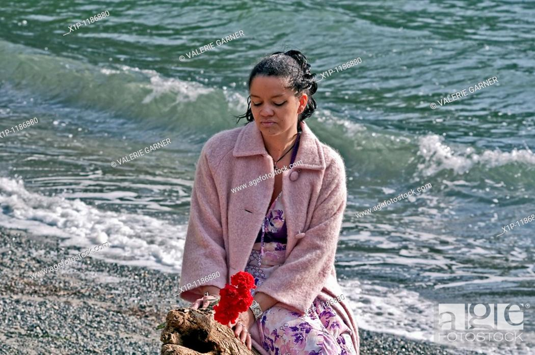Stock Photo: This pretty multi racial woman in her thirties is wearing a pink coat and holding red carnation flowers at the beach Her mood is one of quiet reflection and.