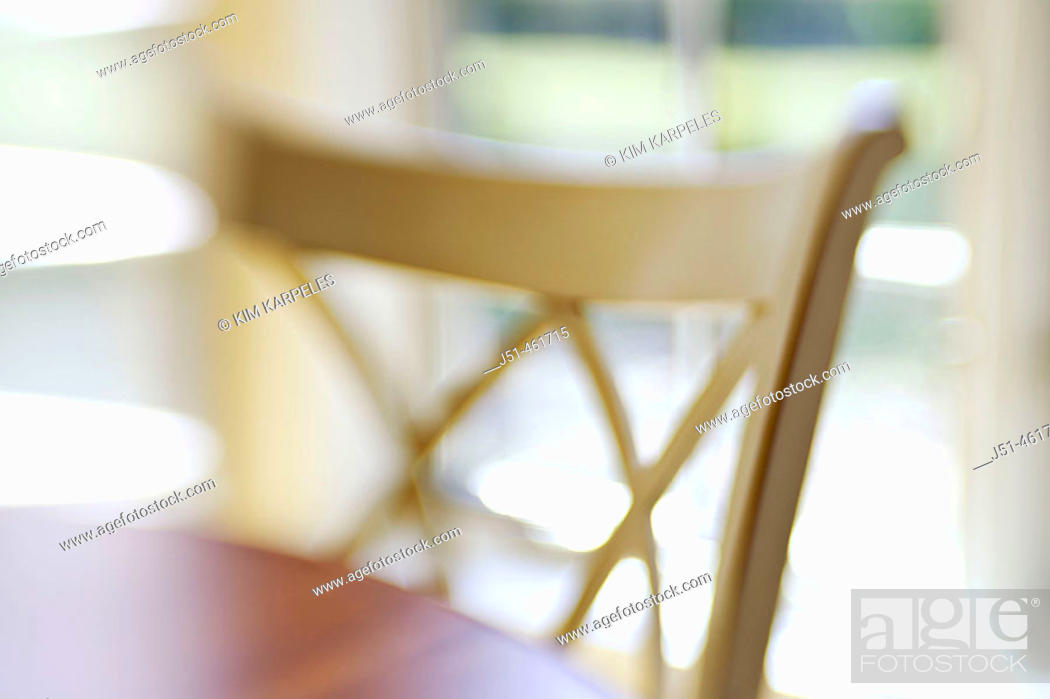 Stock Photo: White wooden chair at wooden table, window behind in eating area, abstract view with selective focus and blur.