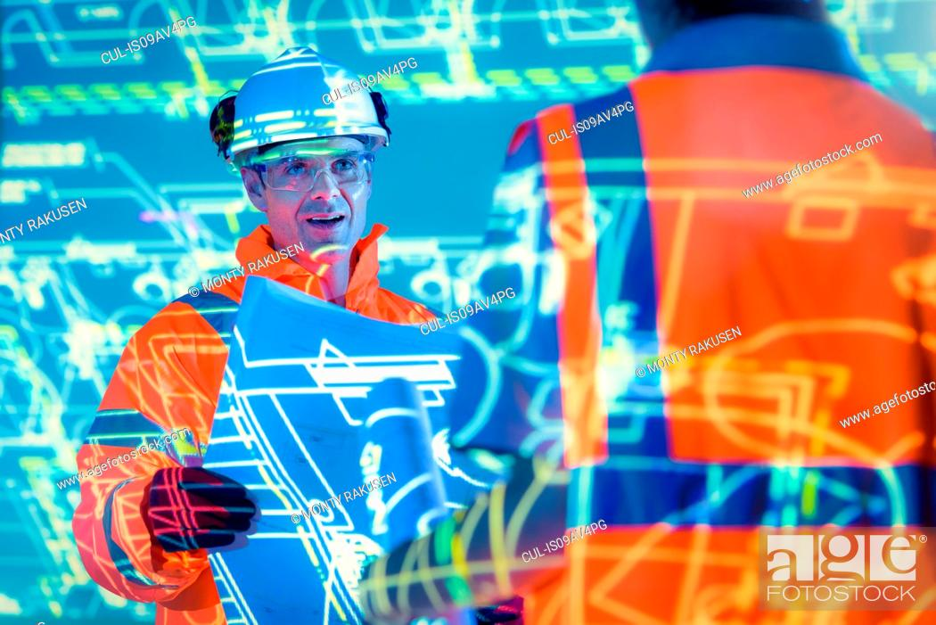 Stock Photo: Engineers with blueprints and projected plans.