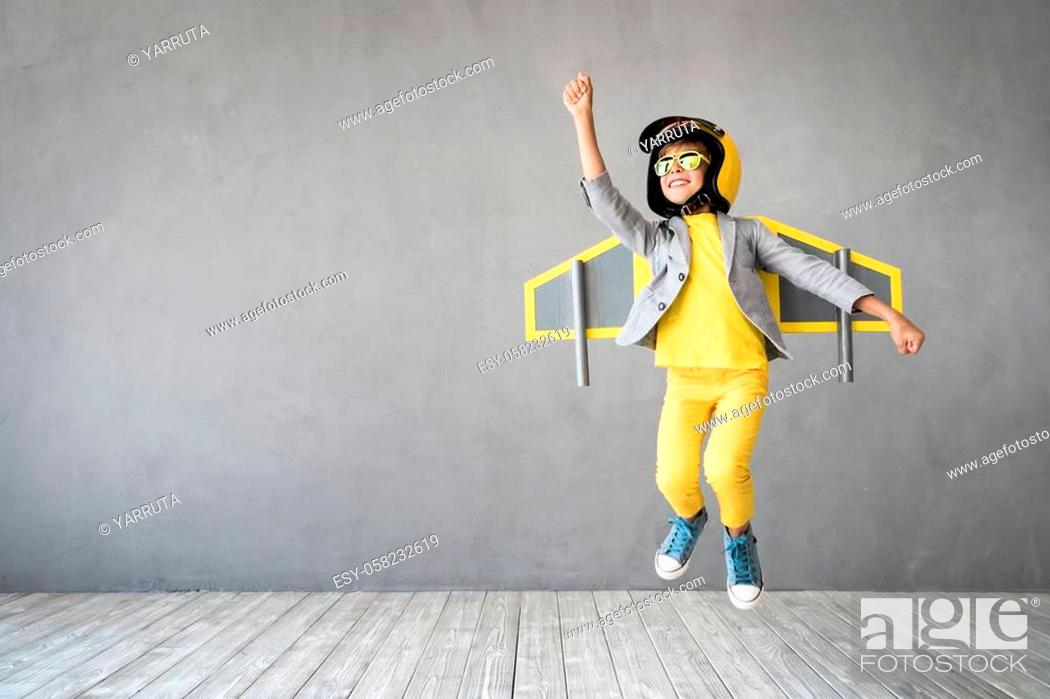 Stock Photo: Happy child playing with toy jetpack. Kid pilot having fun at home. Success, innovation and leader concept.