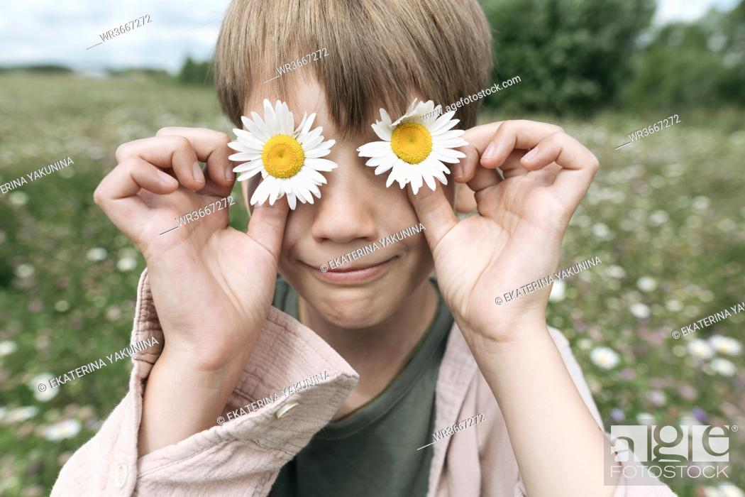 Stock Photo: Close-up of boy hiding eyes with chamomile flowers.