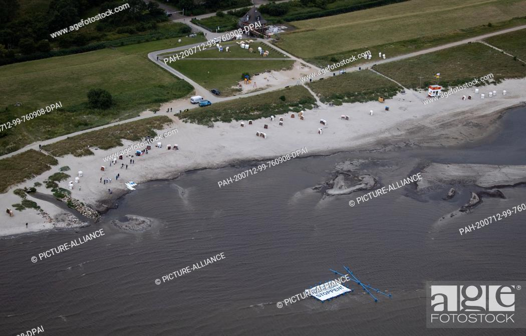 "Stock Photo: 12 July 2020, Schleswig-Holstein, Fehmarn: Supporters and activists of the protest action """"Beltretter"""" hold a banner with the text """"Protect Baltic Sea."