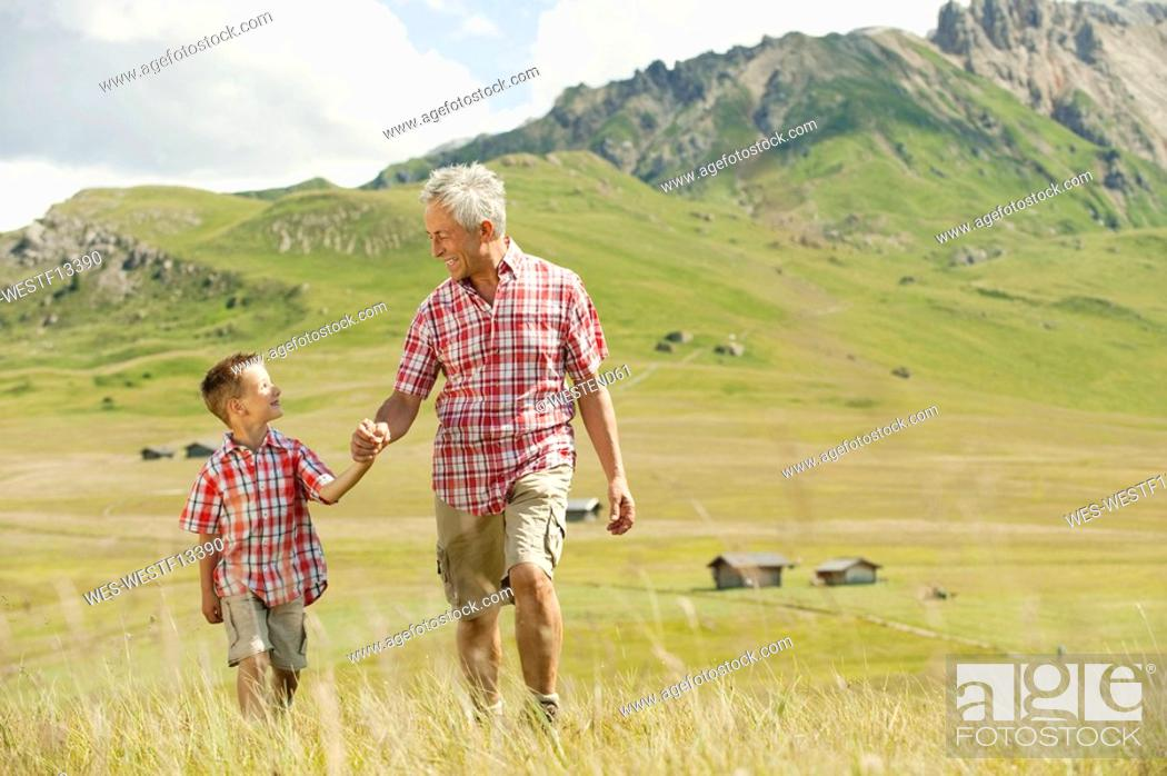 Stock Photo: Italy, Seiseralm, Grandfather and grandson 6-7 walking in field.