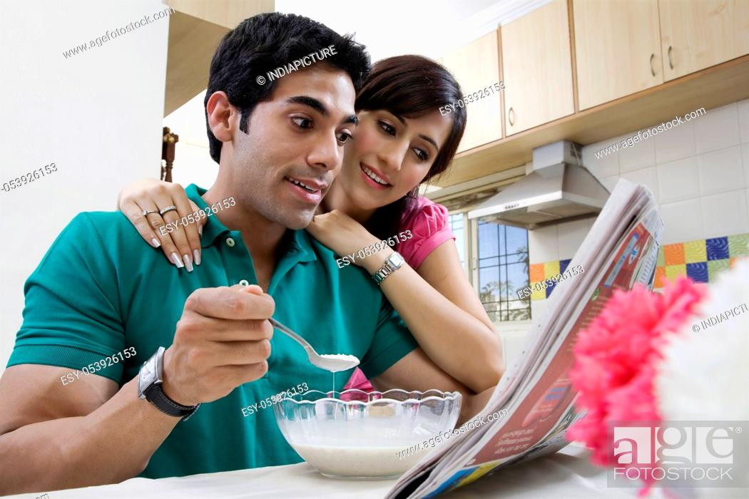 Stock Photo: Couple looking at the morning newspaper.