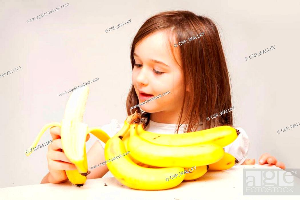 Stock Photo: A young girl is eating a delicious looking yellow banana. She looks like she is enjoying herself.