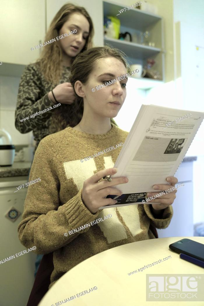 Stock Photo: woman learning with paper transcript in kitchen.