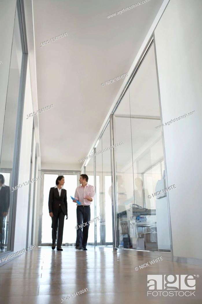 Stock Photo: Two businesspeople walking in hallway of office low angle view.