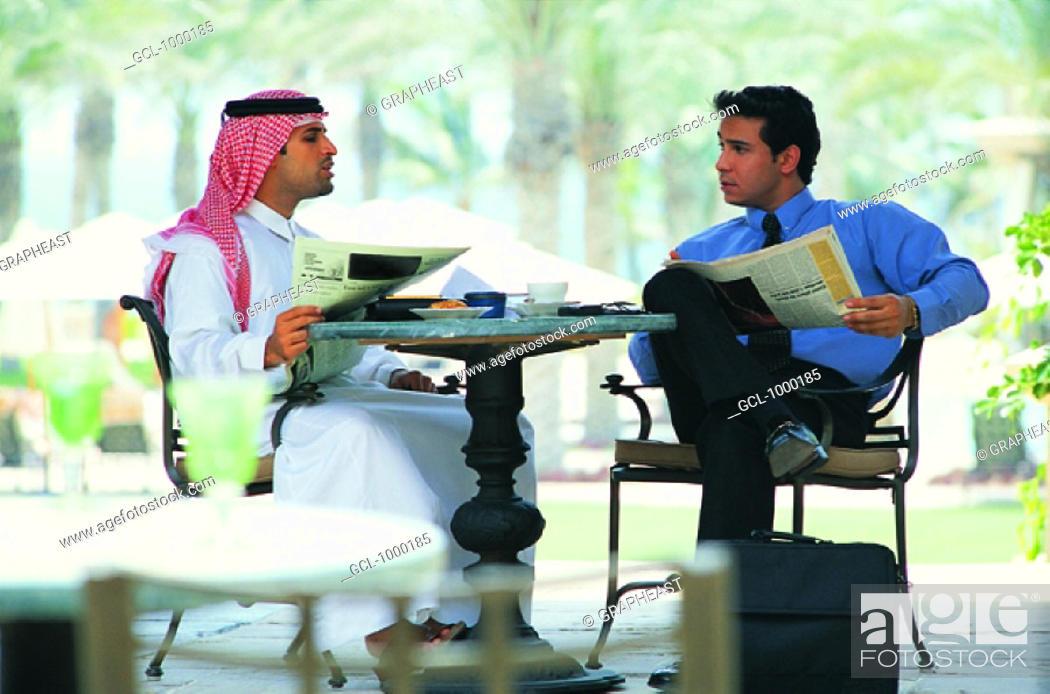 Stock Photo: Arab businessmen reading newspaper.