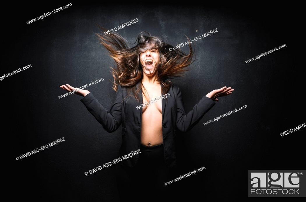 Stock Photo: Portrait of young woman screaming and tossing her hair in front of black background.