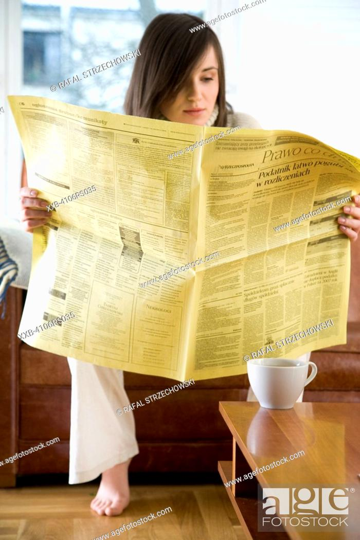 Stock Photo: young woman reading newspaper.