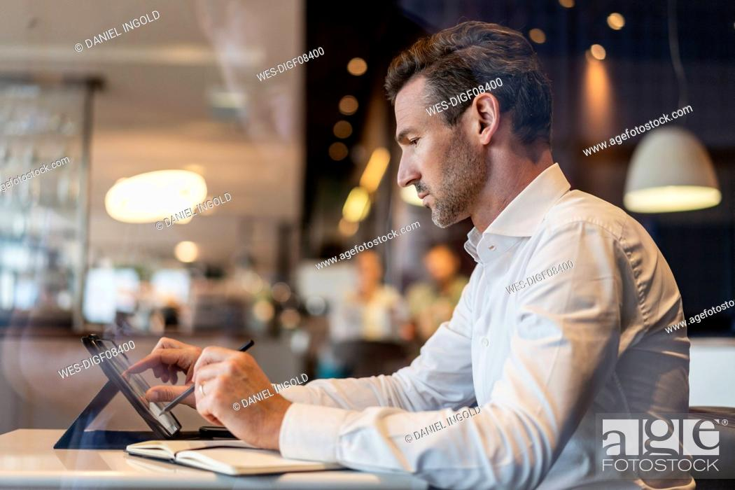 Stock Photo: Businessman using tablet and taking notes in a cafe.
