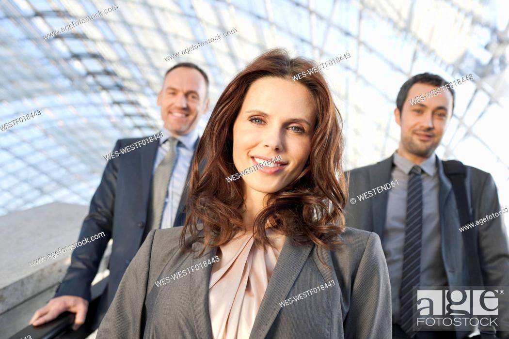 Stock Photo: Germany, Leipzig, Business people on escalator, smiling, portrait.