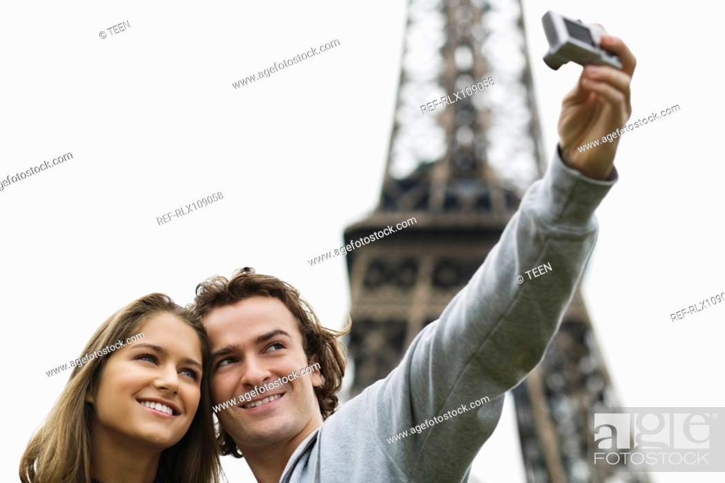 Stock Photo: Young couple taking self portrait in front of Eiffel tower, Paris, France.