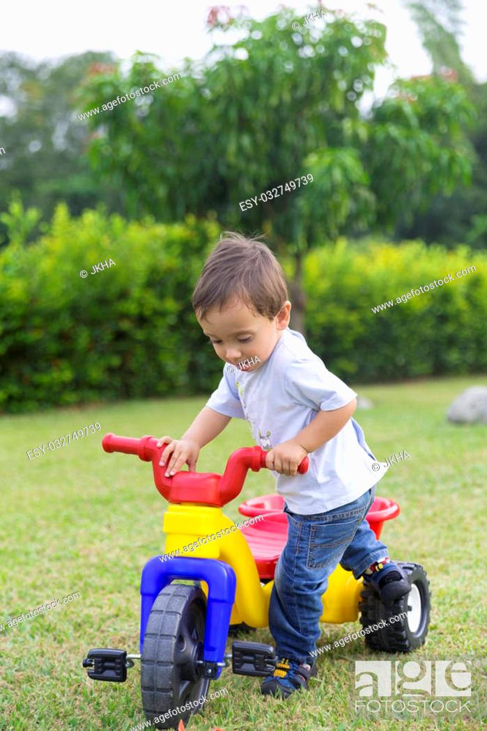 Stock Photo: Happy Little Boy Driving His Toy In The Park.