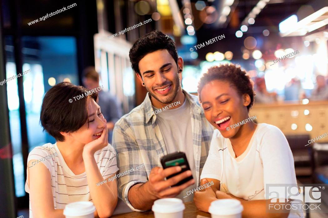Stock Photo: Young friends using cell phone, texting and laughing at cafe.