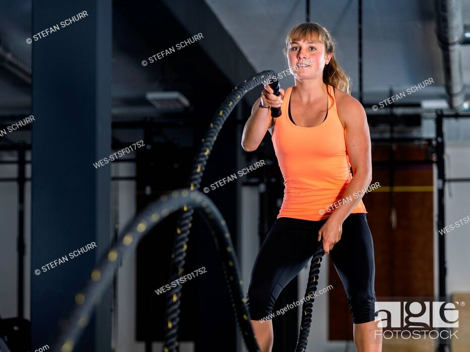 Stock Photo: Athletic young woman exercising with battle ropes at gym.