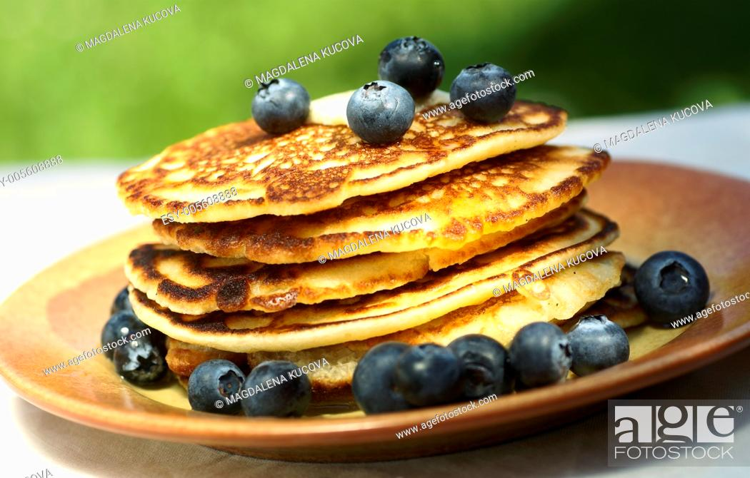 Stock Photo: Stack of pancakes with blueberries on garden table.