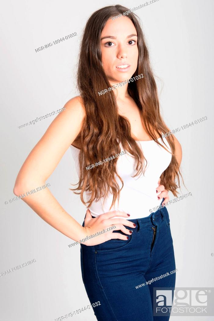 9339fd8bcd Stock Photo - Portrait of young woman with long hair wearing white t-shirt  and blue jeans on white background