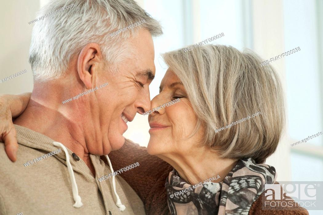 Stock Photo: Germany, Berlin, Senior couple rubbing noses, smiling.