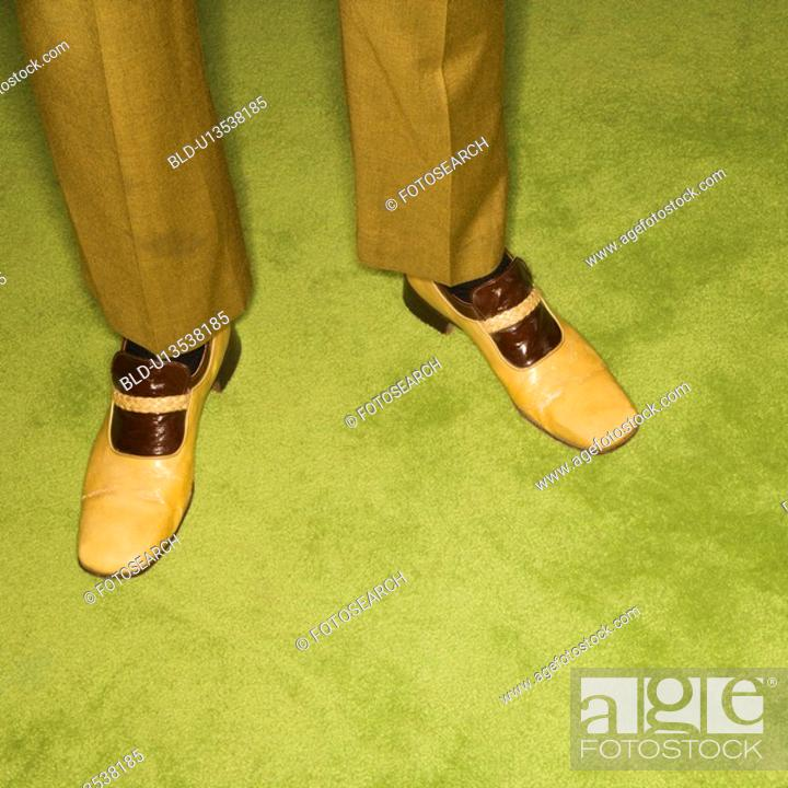 Stock Photo: Close-up of male feet in vintage shoes against green rug.