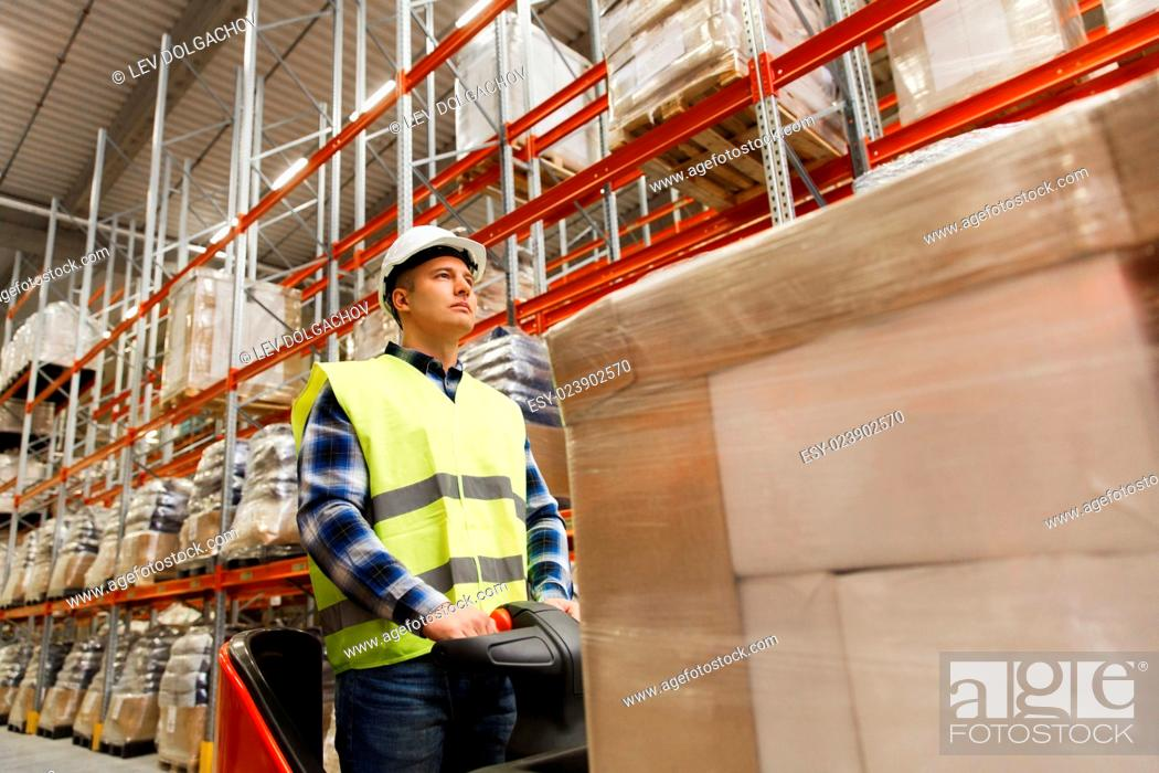 Stock Photo: wholesale, logistic, loading, shipment and people concept - man or loader on forklift loading cargo at warehouse.