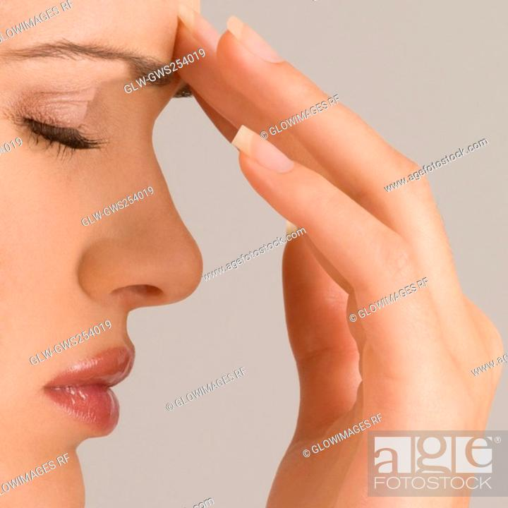 Stock Photo: Close-up of a young woman touching her forehead.