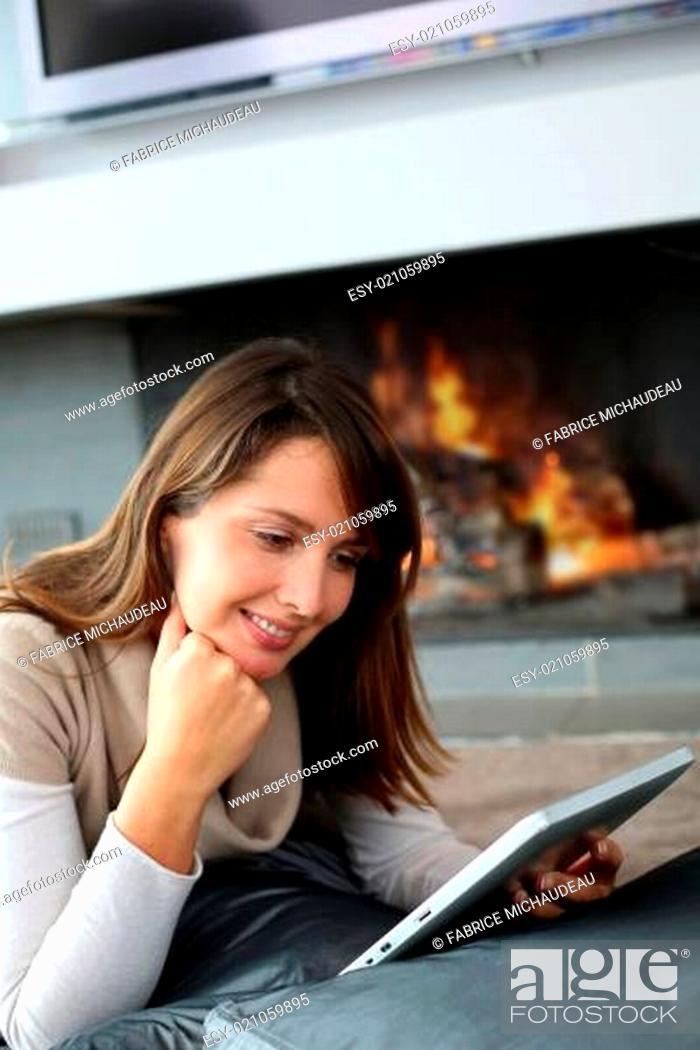 Stock Photo: Woman using digital tablet laying by fireplace.