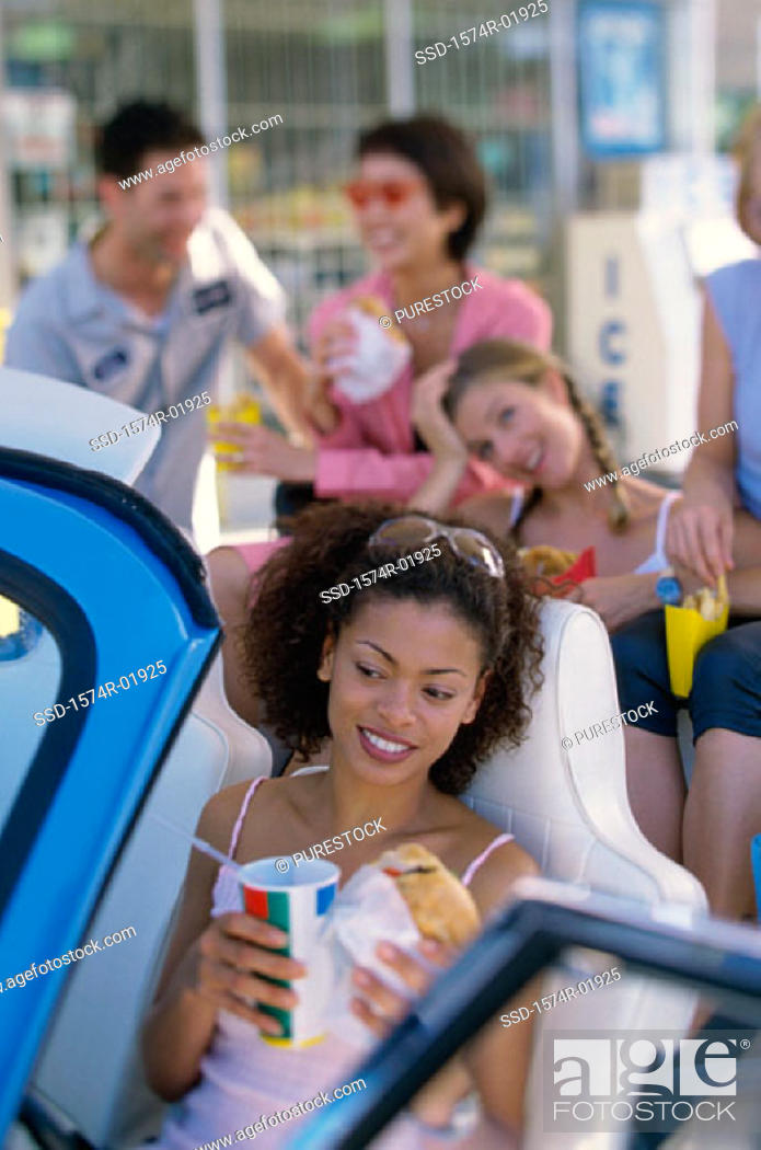 Stock Photo: Group of young men and women eating fast food in a car.