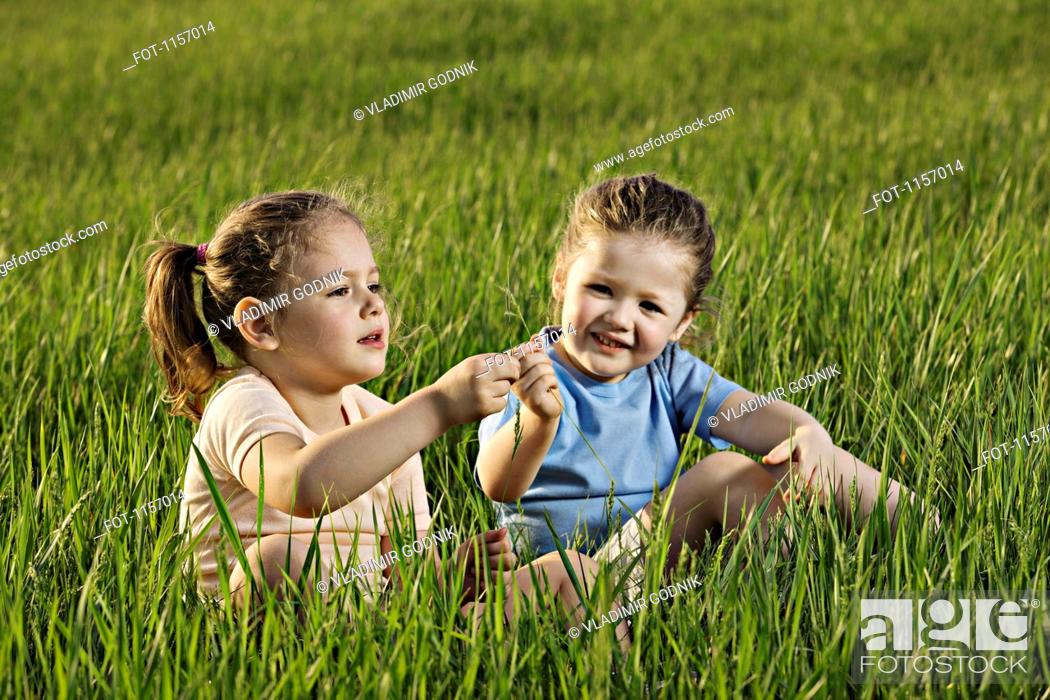 Stock Photo: Two young girls sitting in a field.