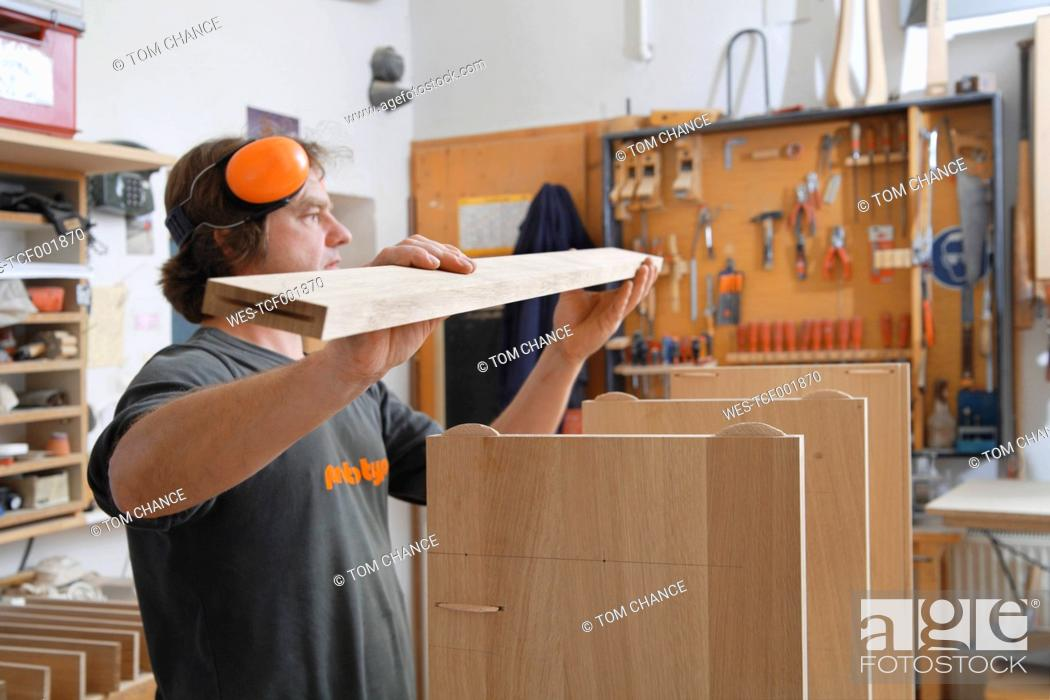 Stock Photo: Germany, Upper Bavaria, Schaeftlarn, Carpenter fixing wood.