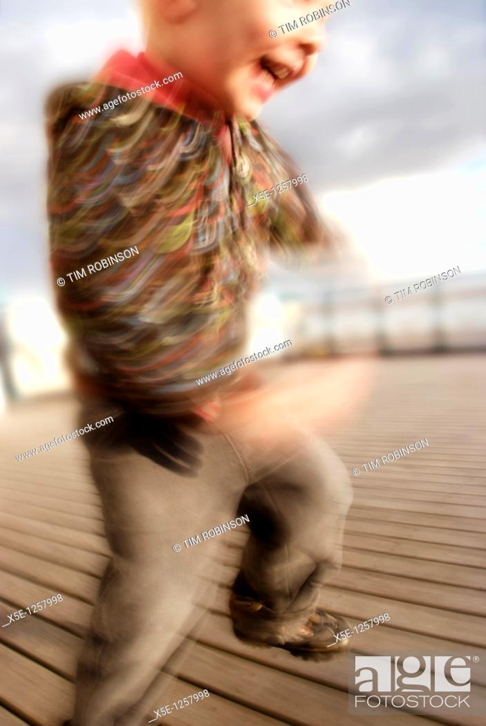 Stock Photo: 4 year boy jumping for joy on pier.