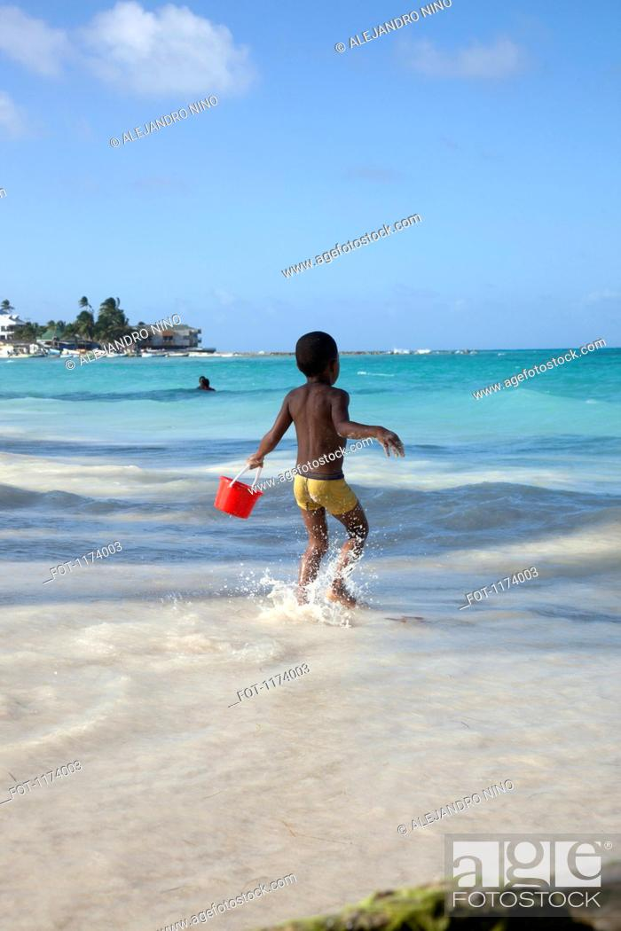 Stock Photo: A young boy running towards the sea holding a sand pail.