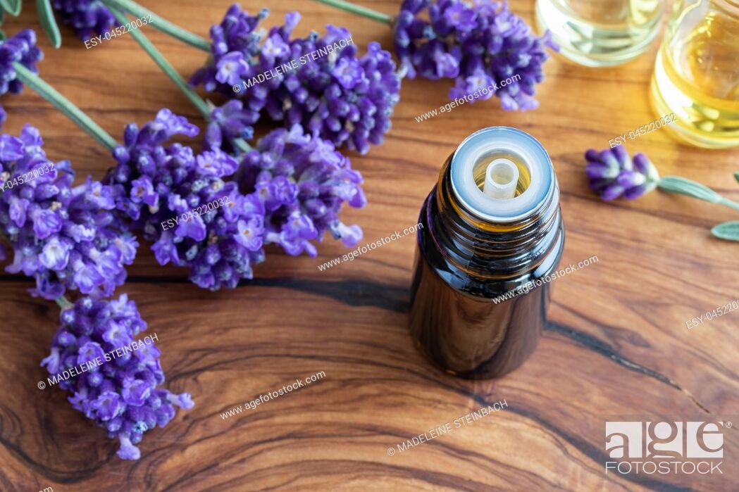 Stock Photo: A bottle of essential oil with fresh blooming lavender on a table.