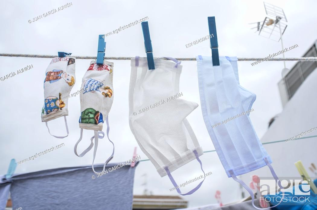 Stock Photo: Set of washable face masks hanging on a clothesline. The set depicts the family together against covid-19.