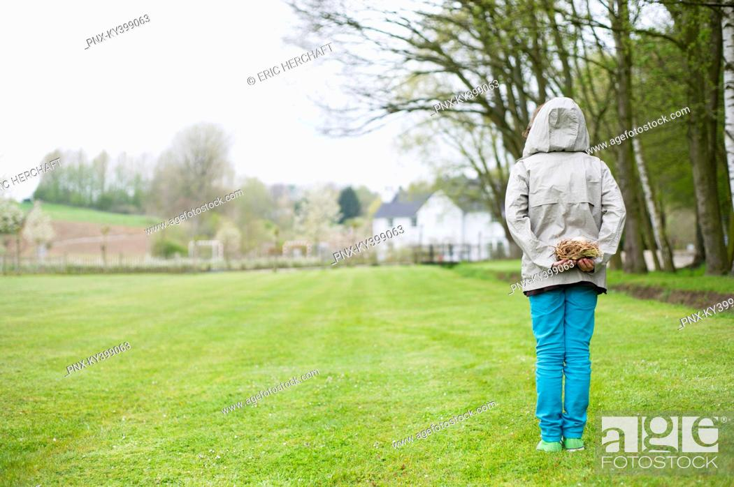 Stock Photo: Rear view of a boy hiding a bird's nest behind his back.