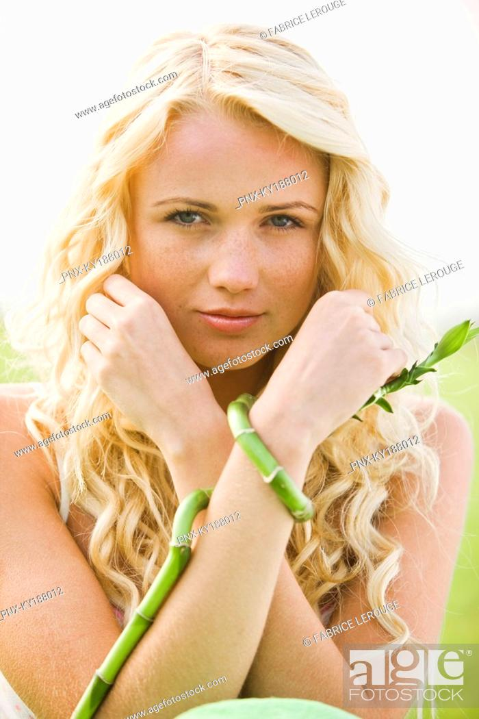 Stock Photo: Young woman holding bamboo.
