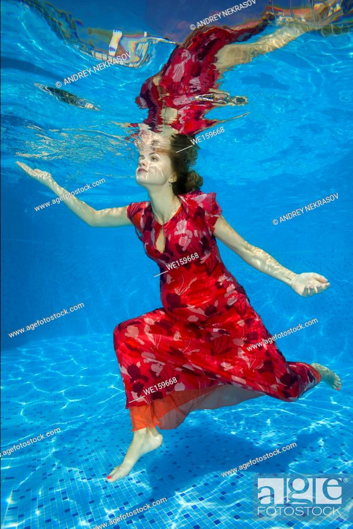 Stock Photo: Young pregnant woman in red dress under water in the pool.