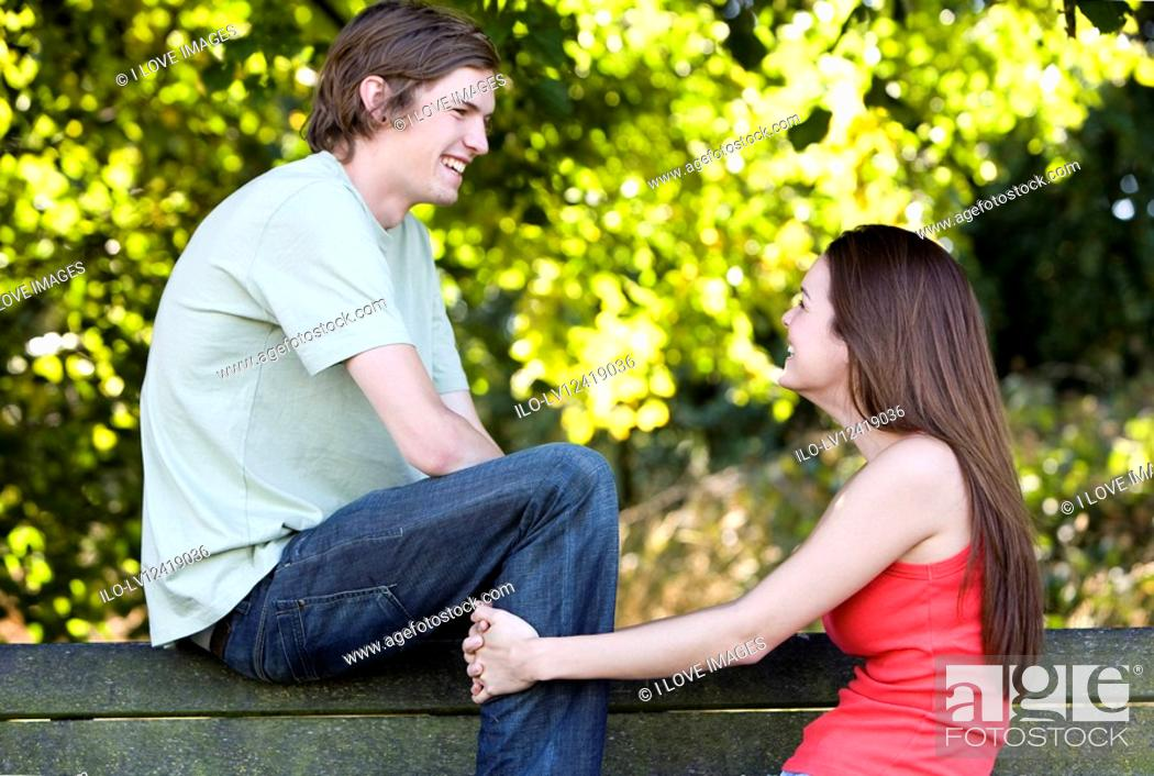 Stock Photo: A young couple talking on a park bench.