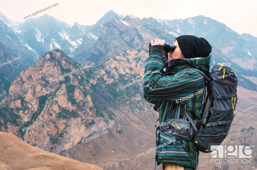 Photo de stock: A hipster man with a beard in a hat, jacket, and a backpack in the caucasian mountains holds binoculars in his hands and looks into the distance, adventure.