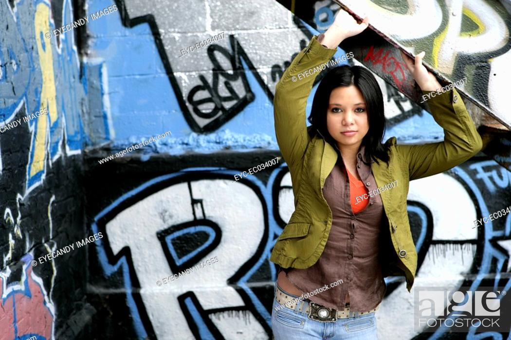Stock Photo: View of a young woman near a graffiti.