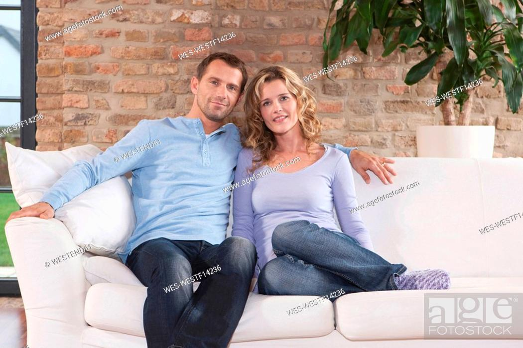 Stock Photo: Germany, Cologne, Couple sitting on sofa, smiling, portrait.