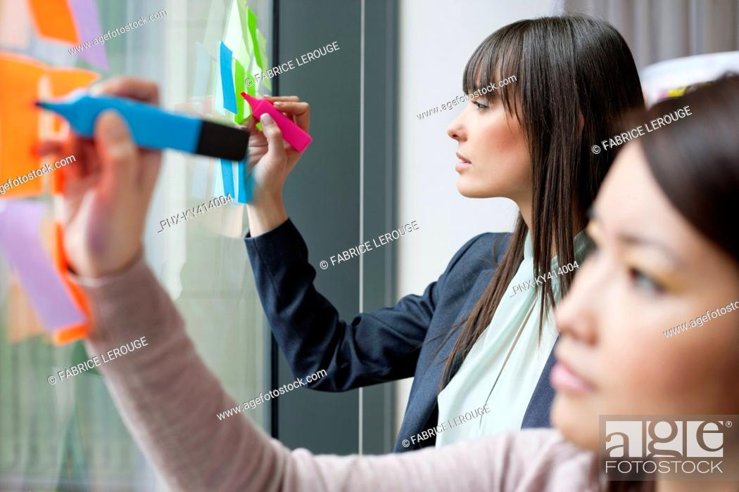 Stock Photo: Businesswomen writing on adhesive notes in an office.