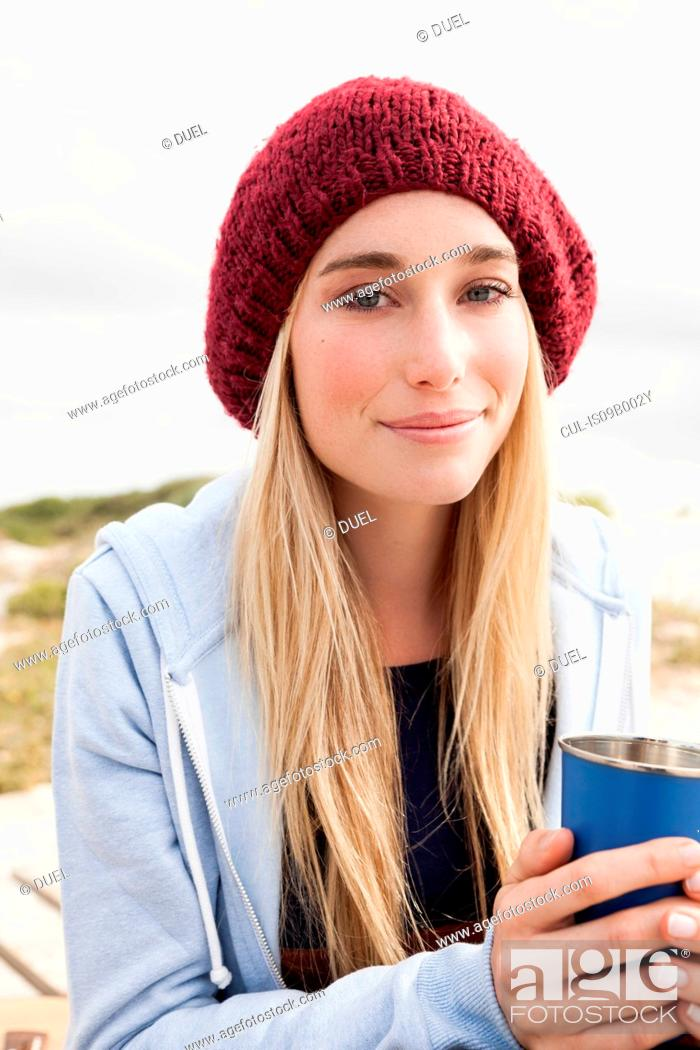 Stock Photo: Young woman holding cup of coffee on cold day.