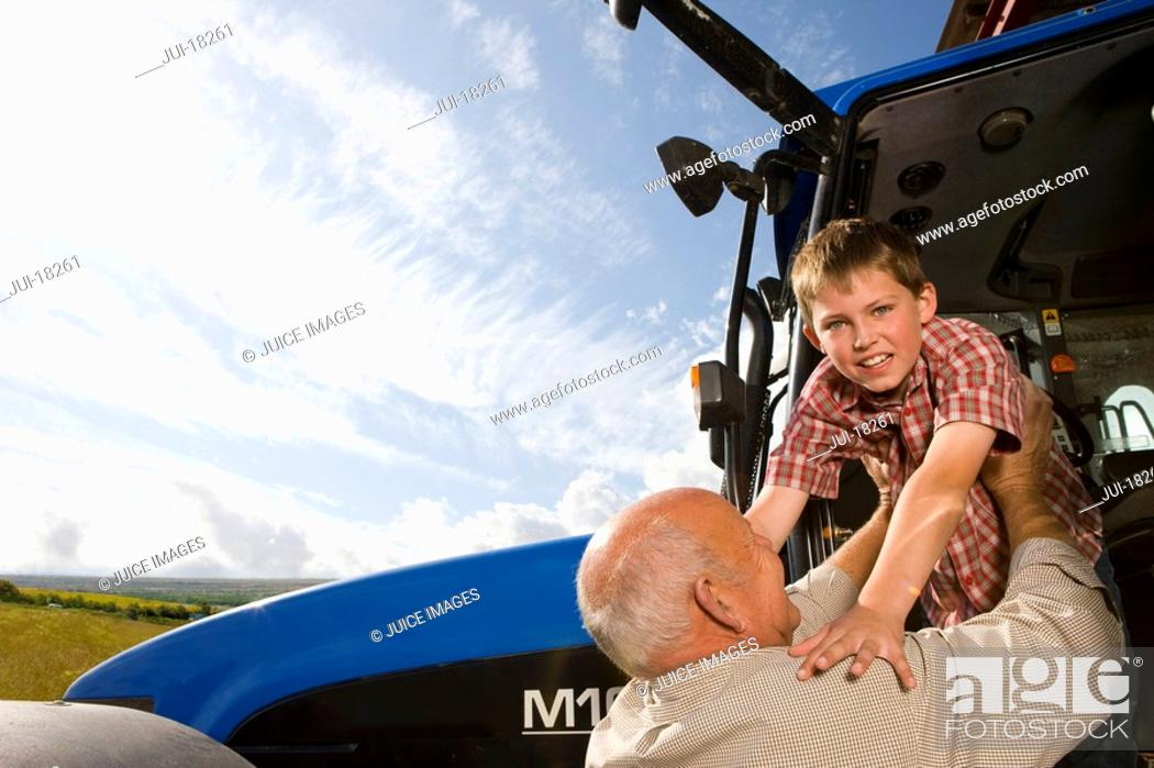 Stock Photo: Farmer helping grandson down from tractor.