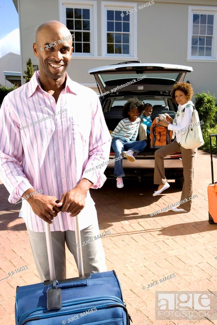 Stock Photo: Man with suitcase in driveway, family by car in background, smiling, portrait.